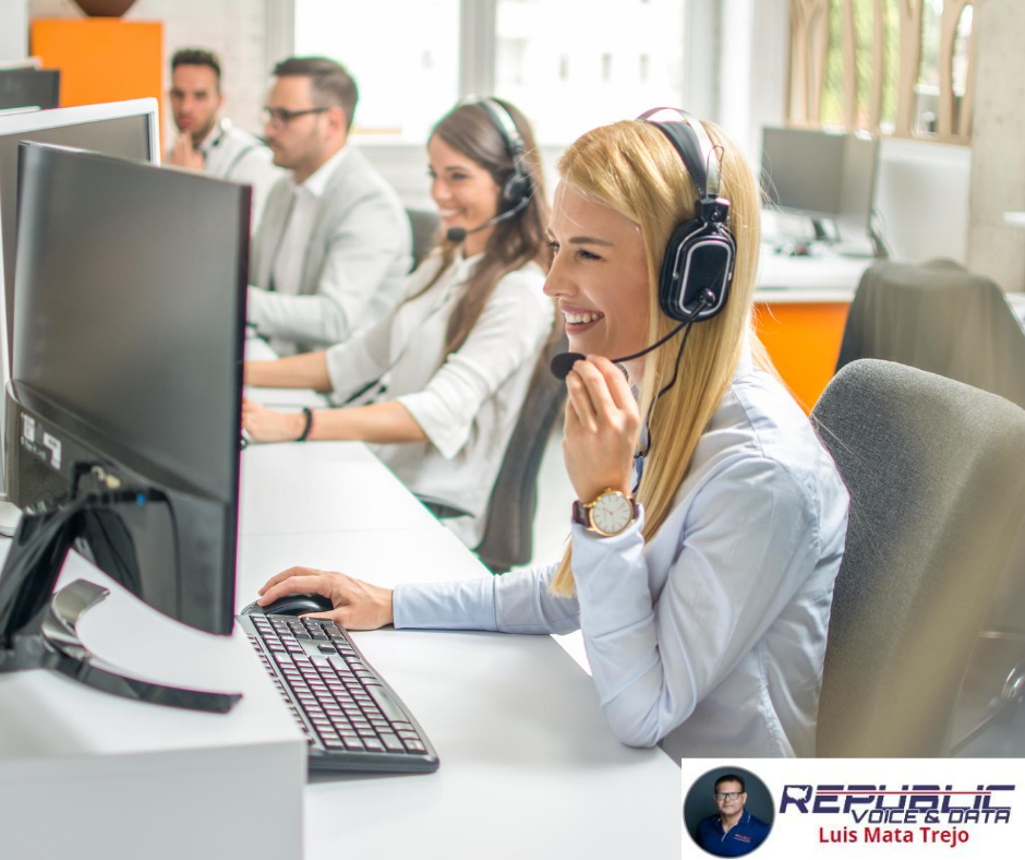 Four call center employees, and a blonde woman in the foreground smiling while using a headset