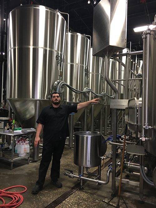 A man showing off the  brewing vats for the Tampa Bay Brewing Co.